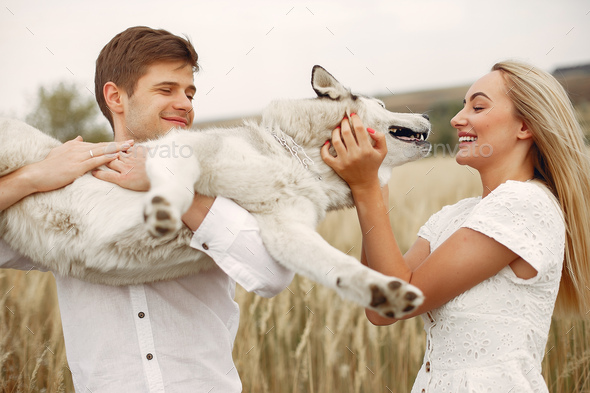 Couple in a autumn field playing with a dog - Stock Photo - Images
