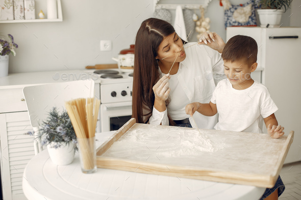 Family sitting in a kitchen and cook the dough for cookies - Stock Photo - Images