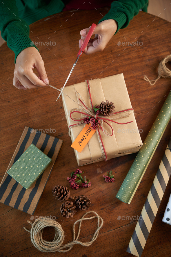 Crop person packing Christmas present - Stock Photo - Images