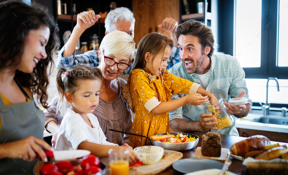 Grandparents, parents and children spending happy time in the kitchen - Stock Photo - Images
