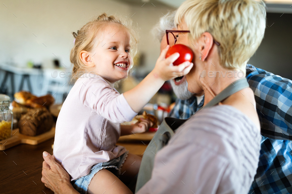 Happy grandparents playing with their little cute granddaughter - Stock Photo - Images