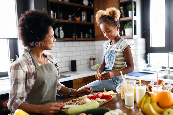 Mother and child having fun preparing healthy food in kitchen - Stock Photo - Images