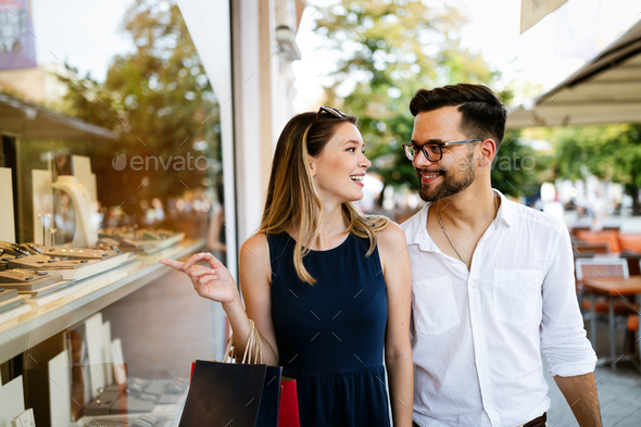 Couple of tourists shopping and walking in a city street - Stock Photo - Images
