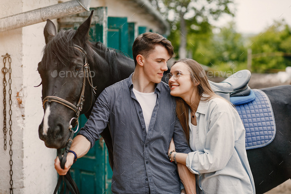 Cute loving couple with horse on ranch - Stock Photo - Images