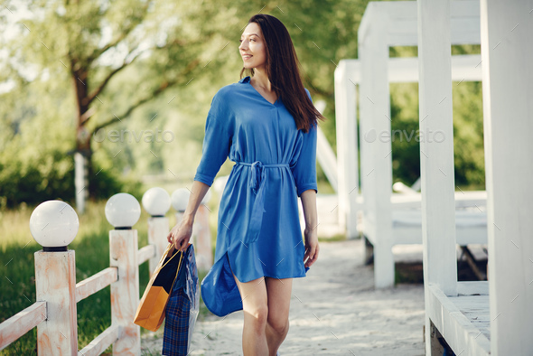 Cute girl with shopping bag in a park - Stock Photo - Images
