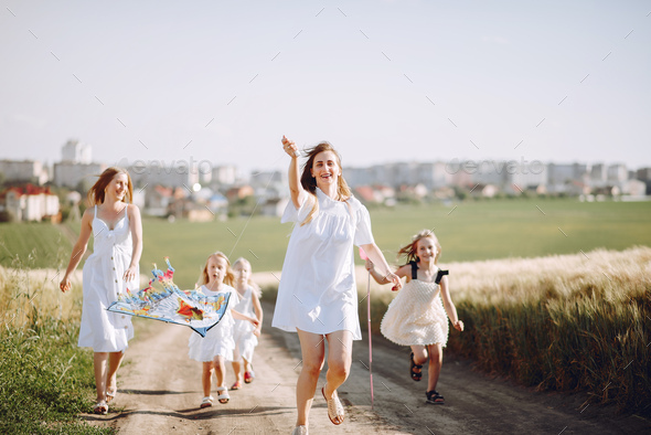 Mothers with daughters playing in a autumn field - Stock Photo - Images