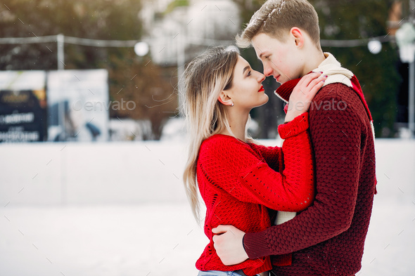 Cute and loving couplein a red sweaters in a winter city - Stock Photo - Images
