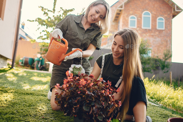 Mother with a daughter works in a garden near the house - Stock Photo - Images