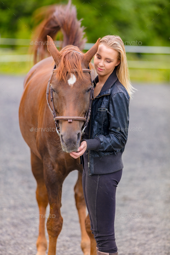 Young woman with her arabian horse standing at a riding course - Stock Photo - Images