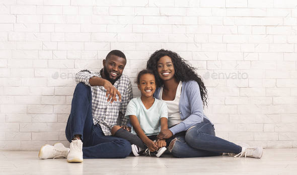 Happy Black Family With Little Daughter Sitting On Floor Together