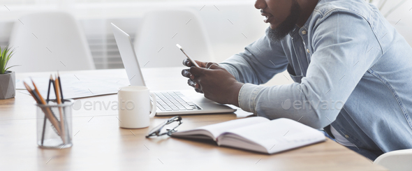 African worker reading message on smartphone during work in office - Stock Photo - Images