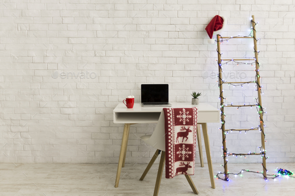 Preparing for Christmas holidays in office over white bricks wall - Stock Photo - Images