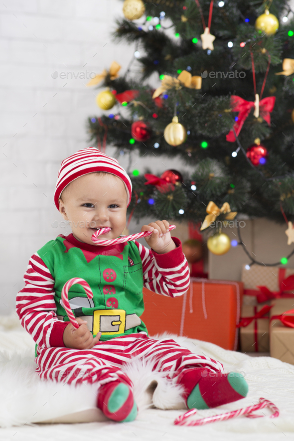Cute baby elf eating lollipop under Christmas tree at home - Stock Photo - Images