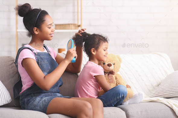 Older african sister taking care of her little sis - Stock Photo - Images