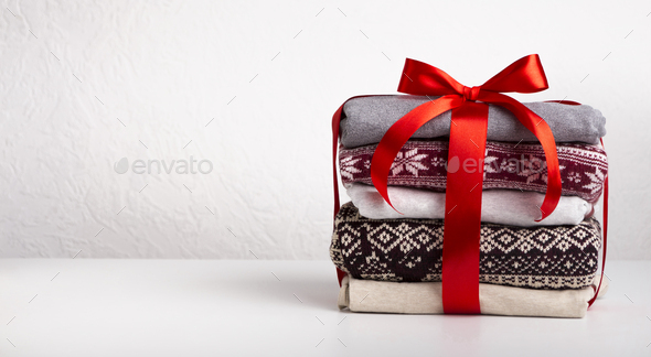 Stack of sweaters wrapped by red ribbon with bow on white - Stock Photo - Images