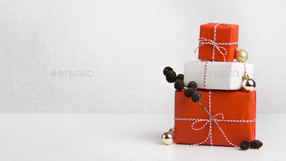 Gift boxes of red and white paper decorated by cones - Stock Photo - Images