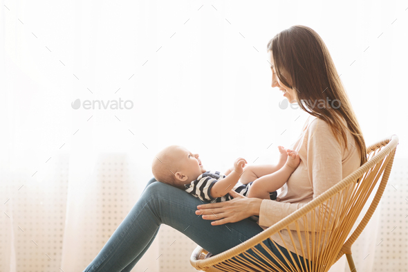 Woman sitting in wicker chair with newborn baby on lap - Stock Photo - Images