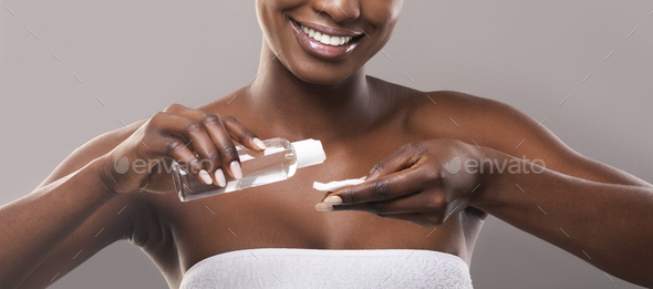 Smiling black woman applying micellar water to cotton pad, crop - Stock Photo - Images