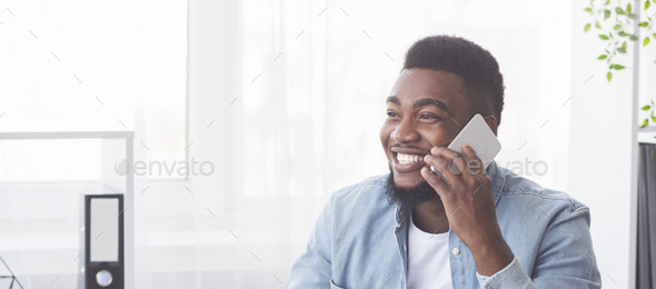 Successful black businessman talking on phone in office - Stock Photo - Images
