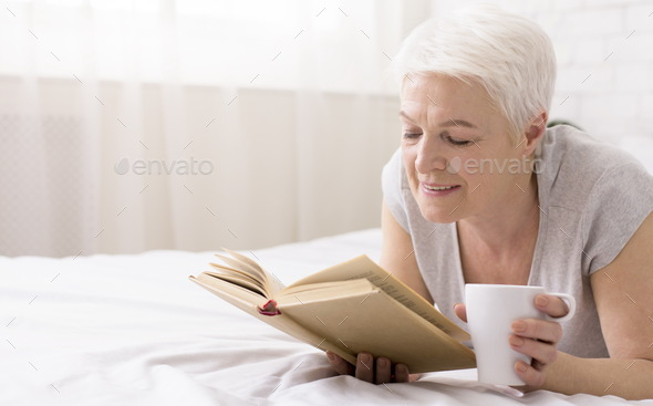 Calm senior woman lying on bed with book and coffee cup - Stock Photo - Images