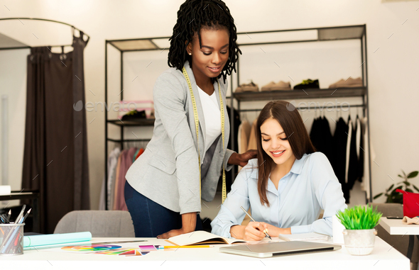 Two Tailors Women Sketching Designing Clothing Collection In Showroom - Stock Photo - Images