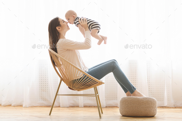 Happy mom spending time with her newborn baby at home - Stock Photo - Images