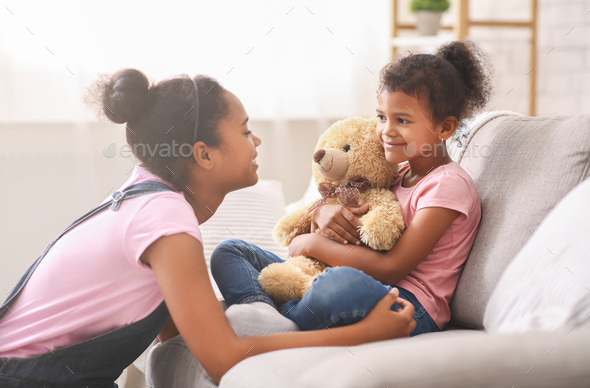 Black teen girl playing with her little sister at home - Stock Photo - Images
