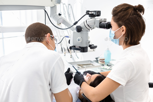 Two dentists making treatment in modern dental clinic - Stock Photo - Images