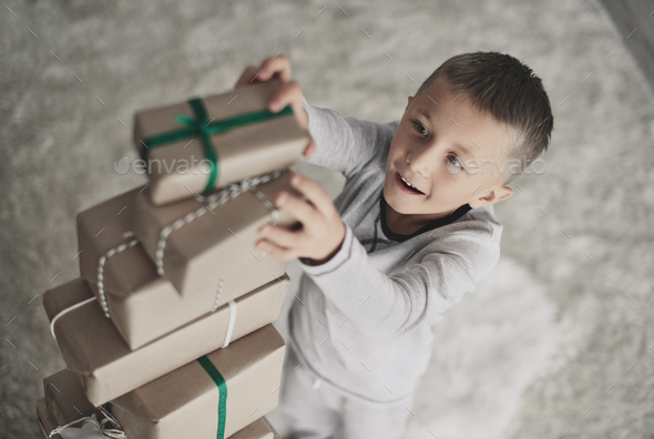 Boy playing and stacking christmas presents - Stock Photo - Images