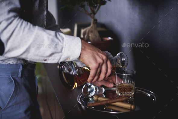Unrecognizable man pouring a glass of whiskey - Stock Photo - Images