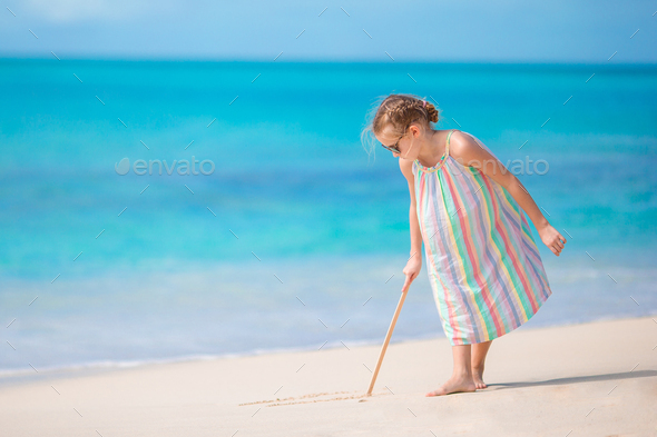 Adorable little girl at beach during summer vacation drawing on sand - Stock Photo - Images