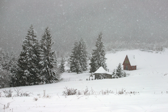 Snow covered hut in the mountains - Stock Photo - Images
