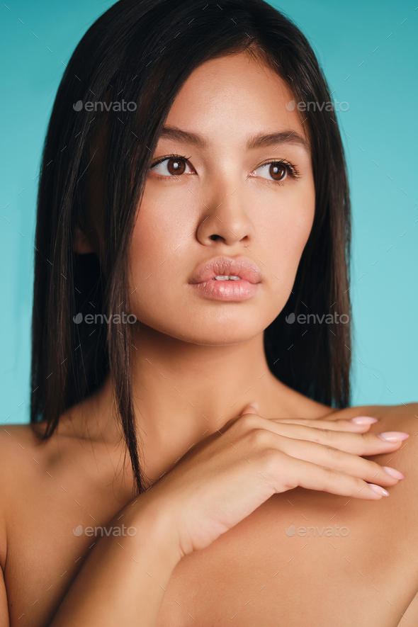 Portrait of gorgeous Asian brunette girl thoughtfully looking away over colorful background - Stock Photo - Images
