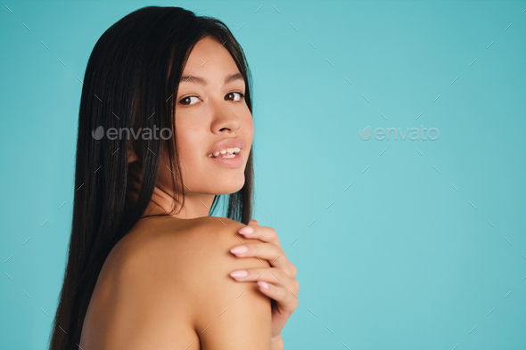 Beautiful Asian brunette girl happily looking in camera over colorful background - Stock Photo - Images