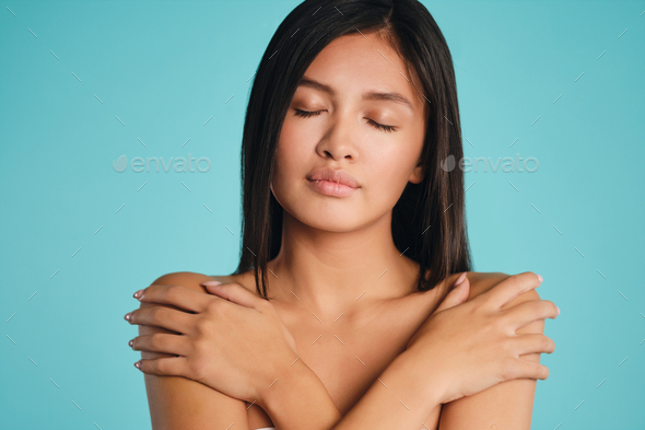 Beautiful tender Asian brunette girl sensually closing eyes over colorful background - Stock Photo - Images