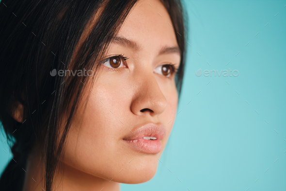 Close up beautiful Asian brunette girl dreamily looking away over colorful background - Stock Photo - Images