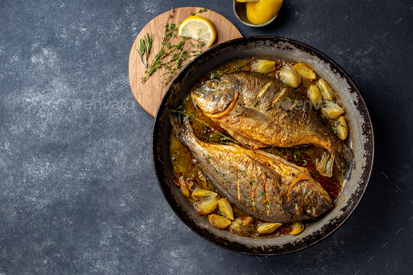 Baked sea bream or dorada with onion and herbs in pan on dark background. - Stock Photo - Images