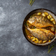 Baked sea bream or dorada with onion and herbs in pan on dark background. - PhotoDune Item for Sale