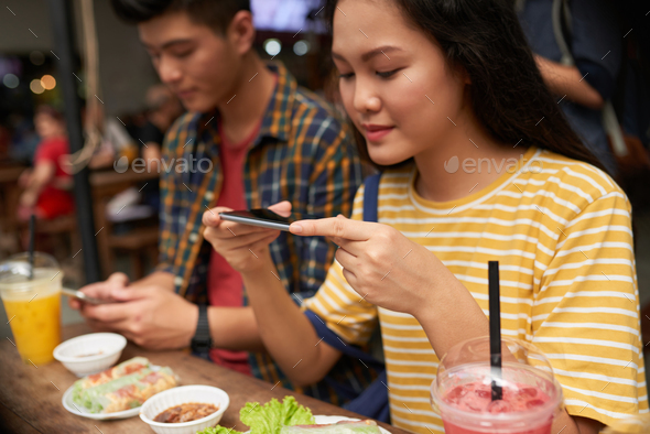 Girl photographing her dinner - Stock Photo - Images