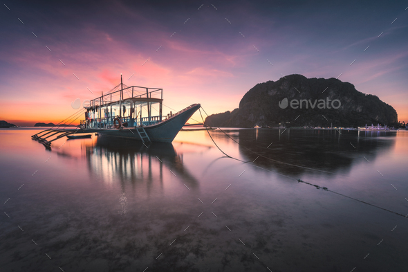 Banca boat at Corong Corong beach on low tide shallow water in twilight lit by sunset light, El Nido - Stock Photo - Images