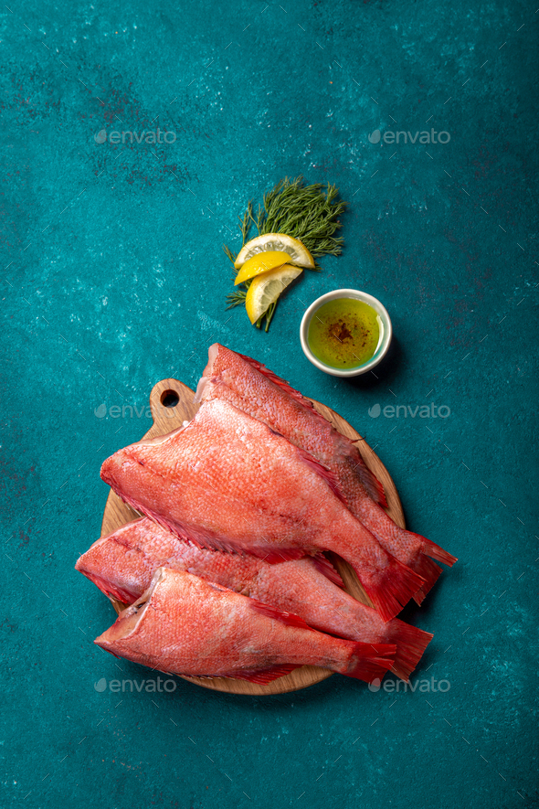 Fresh red sea bass on blue background. - Stock Photo - Images