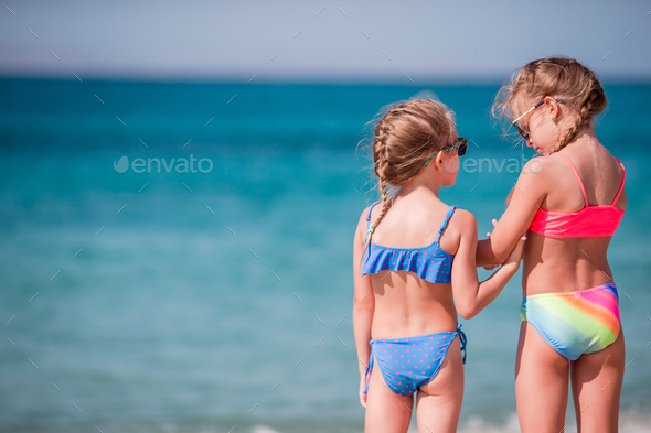 Two little happy girls have a lot of fun at tropical beach playing together - Stock Photo - Images
