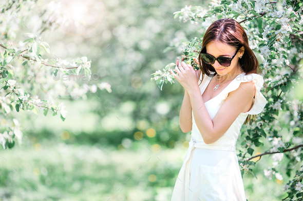 Beautiful woman enjoying smell in spring cherry garden - Stock Photo - Images