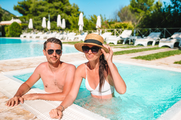 Cheerful couple resting in a swimming pool - Stock Photo - Images