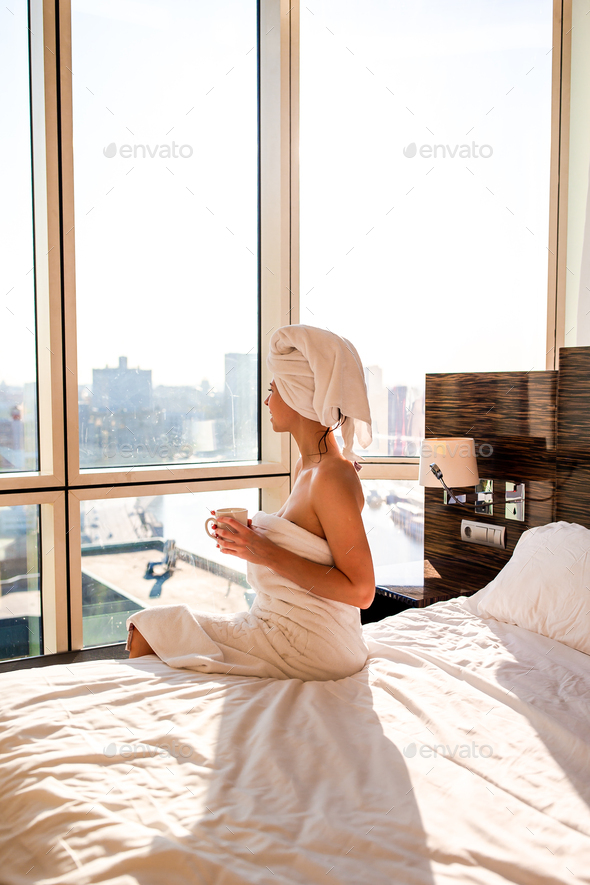 Beautiful young woman in white bath towel on head relaxing after shower on bed with cup of coffee - Stock Photo - Images