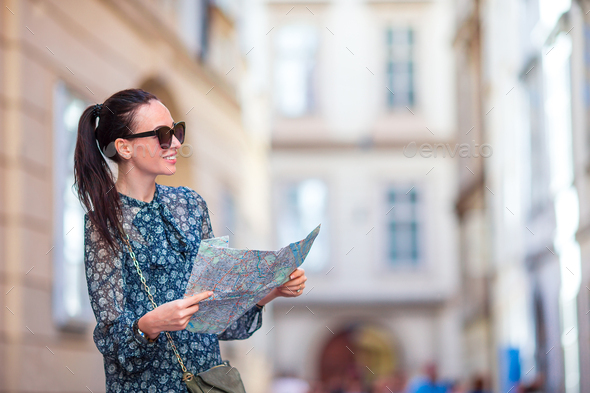 Young woman with a city map in city. Travel tourist girl with map in Vienna outdoors during holidays - Stock Photo - Images
