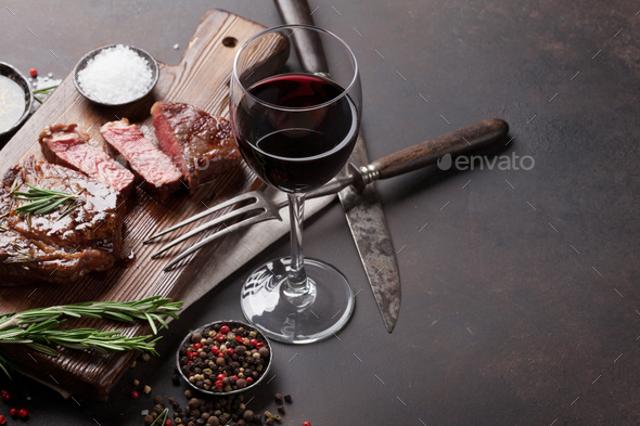 Grilled ribeye beef steak with red wine, herbs and spices - Stock Photo - Images