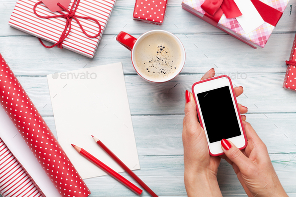 Female holding smartphone and wrapping christmas gifts - Stock Photo - Images