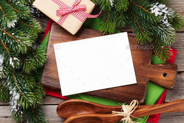 Christmas greeting card over cooking table and utensils - Stock Photo - Images