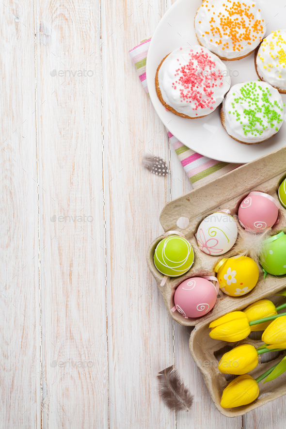 Easter with yellow tulips, colorful eggs and traditional cakes - Stock Photo - Images